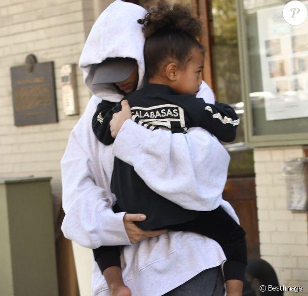 Kim Kardashian, cachée par ses vêtements, et sa fille North sortent de son appartement à New York, le 6 octobre 2016.