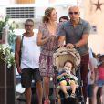 Exclusif - Eric Judor et sa compagne font une pause tendresse dans la rue à Saint-Tropez lors d'une balade avec leur fils le 17 août 2016.