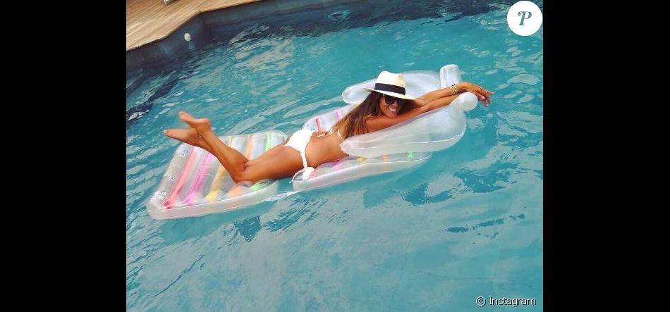 Karine Ferri dévoile sa silhouette de rêve en bikini, lors de ses vacances au bord d'une piscine en août 2017.