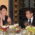 D'un geste de mannequin, Carla Bruni met son oreillette sous le regard admiratif de son époux