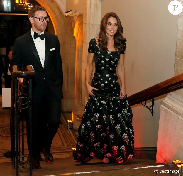 """La duchesse Catherine de Cambridge (Kate Middleton), en robe Alexander McQueen, à la National Portrait Gallery en compagnie de son directeur Nicholas Cullinan lors du gala du musée """"Inspiring People"""", le 12 mars 2019 à Londres."""