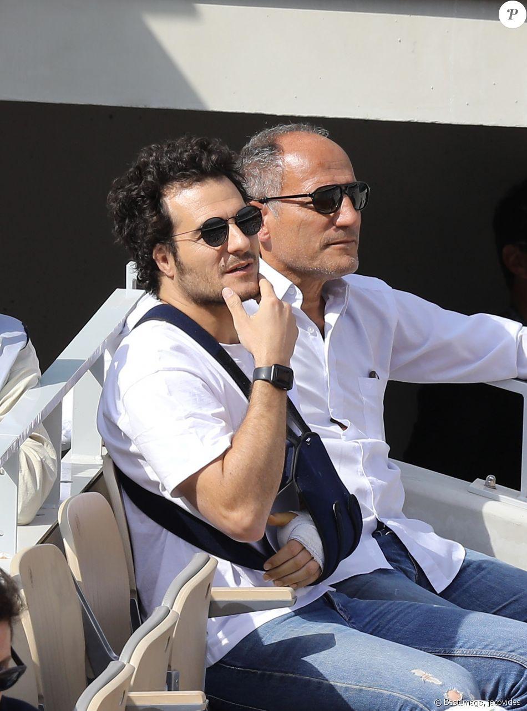Amir Haddad (le bras gauche dans le plâtre après être tombé de scène pendant un concert à Aubagne) et son père René-Mikhael Haddad dans les tribunes des internationaux de tennis de Roland Garros à Paris, France, le 27 mai 2019. © Jacovides-Moreau/Bestimage