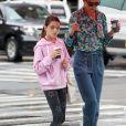 Katie Holmes et sa fille Suri marchent à New York sous un parapluie rose le 21 juin 2019.