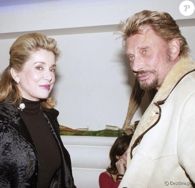 """Catherine Deneuve et Johnny Hallyday lors d'une soirée organisée par l'office du tourisme d'Afrique du Sud au restaurant """"La Suite"""", à Paris, le 1 février 2004."""