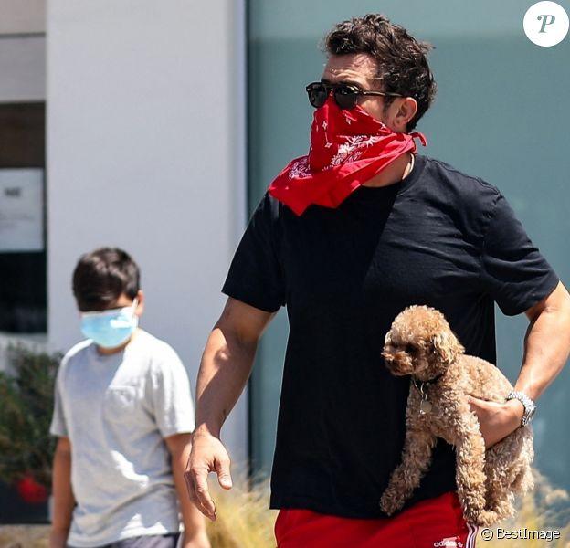 Exclusif - Orlando Bloom passe un moment complice avec son fils Flynn à Brentwood le 19 mai 2020. En marge d'une balade avec le chien, ils se posent sur un banc pour écouter de la musique sur le téléphone d'Orlando.