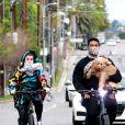 Exclusif - Usher et sa compagne Jennifer Goicoechea, avec un foulard en guise de masque de protection pour chacun d'eux, se promènent à vélo avant de faire une halte dans un parc du quartier de Los Feliz à Los Angeles, pendant le confinement lié au coronavirus (Covid-19), le 5 avril 2020.