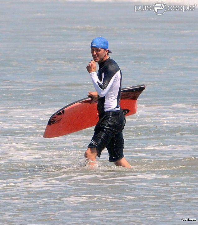 David Beckham ne quitte pas sa casquette bleue pour surfer à Malibu, le 30 juillet 2011.