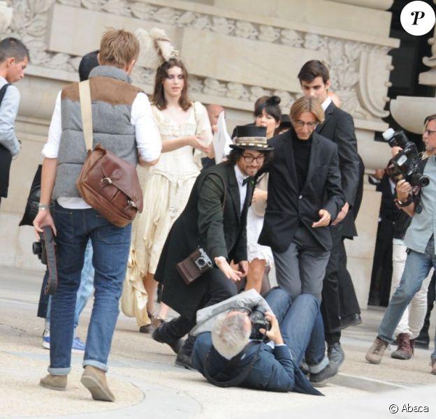 Sean Lennon aide un photographe à se relever en marge du défilé Chanel le 4 octobre 2011 au Grand Palais