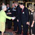 La reine Elizabeth II, qui salue ici Mark Dickens, descendant de l'écrivain, donnait le 14 février 2012 une réception à Buckingham Palace suite à la représentation d'une pièce hommage à Charles Dickens au Guildhall de Londres.