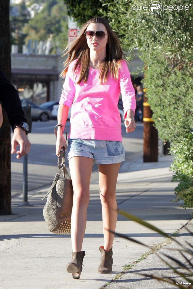 Miranda Kerr, radieuse et stylée avec un sweater rose bonbon J Crew, une minijupe et des bottines Isabel Marant et un sac Alexander Wang. Los Angeles, le 2 avril 2012.