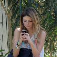 L'actrice Mischa Barton en tête à tête avec son iPhone 4S lors du Festival de Coachella. Indio, le 14 avril 2012.