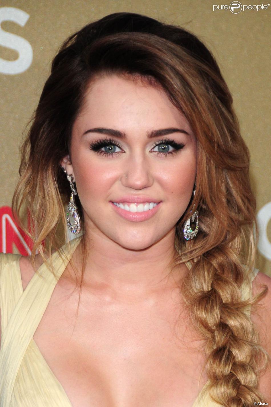 Miley Cyrus avec un ombré hair et des cheveux longs tressés.