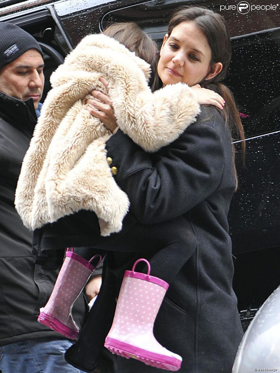 Suri Cruise et Katie Holmes dans les rues de New York, le 8 mars 2013. La petite fille ne daigne pas mettre un pied sur le sol à cause de la neige.