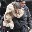 Suri Cruise dans es bras de sa mère Katie Holmes dans les rues de New York, le 8 mars 2013. La petite fille ne daigne pas mettre un pied sur le sol à cause de la neige.