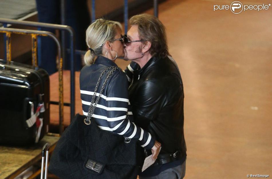 Johnny et Laeticia Hallyday partagent un baiser à leur arrivée en France avec leurs filles Joy et Jade et Eliette (la grand-mère de laeticia), à Paris le 21 mai 2013.