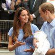 Le duc et la duchesse de Cambridge, rayonnante au lendemain de son accouchement, quittant la maternité de l'hôpital St Mary le 23 juillet 2013 avec leur bébé le prince de Cambridge.