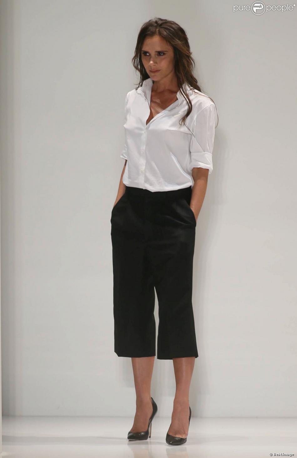 Victoria Beckham, ultra chic en chemise blanche, pantalon noir et souliers Manolo Blahnik, salue son public à l'issue de son défilé printemps-été 2014. New York, le 8 septembre 2013.