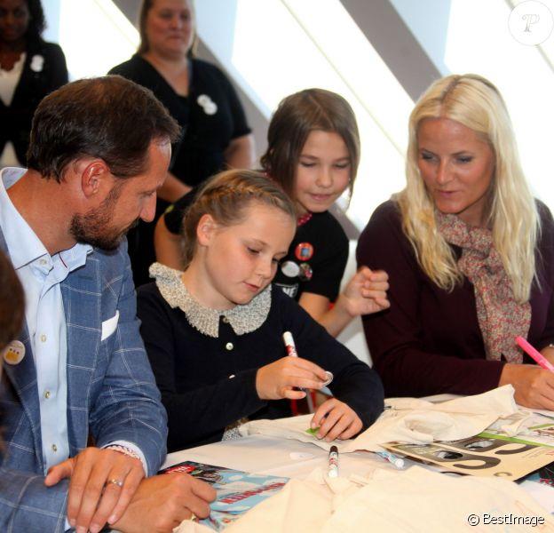 """Le prince Haakon, la princesse Mette-Marit et leur fille la princesse Ingrid Alexandra de Norvège, ici très appliqués lors d'un atelier, inauguraient le 13 septembre 2013 à Oslo la Maison de l'Environnement (""""Miljohuset"""")."""
