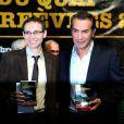 Jean Dujardin et le lauréat lors de la remise du prix polar Quai des Orfèvres 2014 à Hervé Jourdain, capitaine à la Crim', pour son livre Le sang de la trahison, à Paris, le 12 novembre 2013.