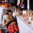Michelle Obama embrasse la petite Ashtyn Gardner, 2 ans, lors de la présentation des décorations de Noël de la Maison Blanche. Washington, le 4 décembre 2013.