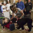 Michelle Obama relève et rassure l'adorable Ashtyn Gardner (2 ans), chahutée par son chien Sunny lors de la présentation des décorations de Noël de la Maison Blanche. Washington, le 4 décembre 2013.