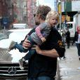 """Eric Johnson, mari de Jessica Simpson, porte sa fille Maxwell dans les rues de New York, le 5 décembre 2013."""
