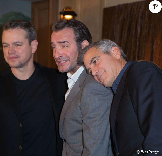 """Matt Damon, Jean Dujardin et sur son épaule, George Clooney lors du photocall du film """"Monuments Men"""" à l'hôtel Bristol à Paris le 12 février 2004."""