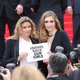 Lisa Azuelos et Julie Gayet (pancarte pour les lycéennes enlevées au Nigéria)   lors de la montée des marches du film Saint Laurent et l'hommage au cinéma d'animation au Festival de Cannes le 17 mai 2014