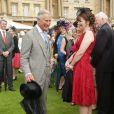 Le prince Charles profite d'une éclaircie pour ranger son parapluie lors de la pluvieuse troisième garden party de l'année organisée à Buckingham Palace le 3 juin 2014.