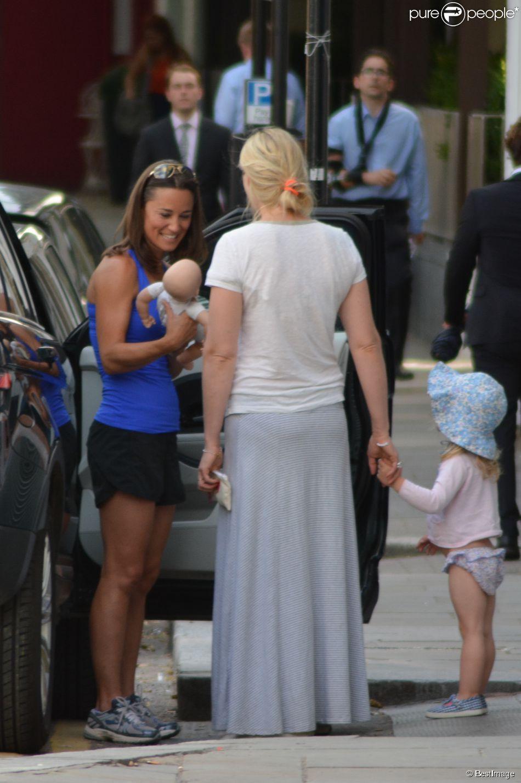 Exclusif - La superbe Pippa Middleton, un poupon dans les bras, discute avec une amie à Londres, le 14 juillet 2014.