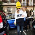 Cara Delevingne porte un bonnet jaune de sa collection CaraD4DKNY pour DKNY, un pull DKNY, un jean et des bottines Timberland. Londres, le 8 octobre 2014.
