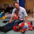 Le prince Harry avec des enfants suivant un programme contre la malnutrition à Maseru, le 8  décembre 2014 lors de sa visite privée pour suivre les actions de son association Sentebale.