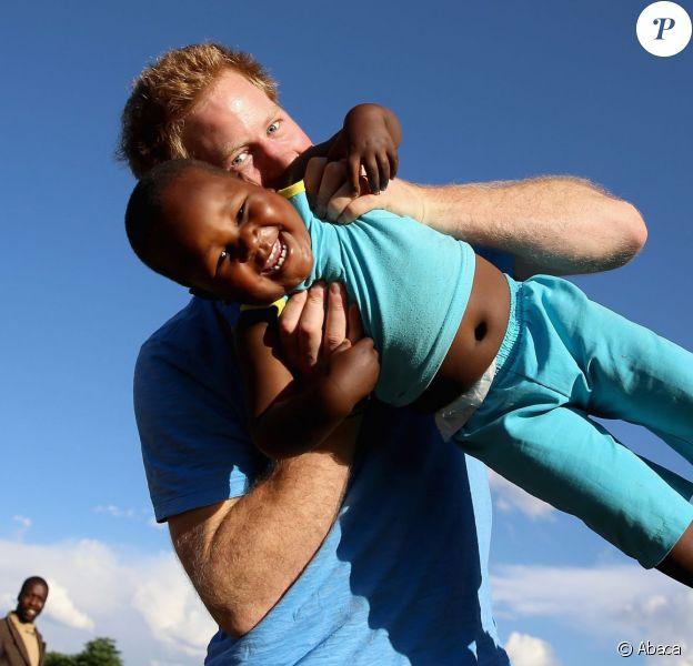 Le prince Harry soulève le jeune orphelin Lerato tandis que la petite non-voyante Karabo prend la photo, le 6 décembre 2014 dans un orphelinat de Maseru, lors de sa visite privée pour suivre les actions de son association Sentebale.
