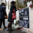 Une femme dépose des fleurs devant les bureaux de Charlie Hebdo le 7 janvier 2014