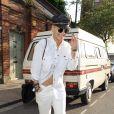 Rita Ora quitte un studio d'enregistrement à Londres, habillée d'une chemise et d'un jean blancs Levi's, et de bottines vernies. Une casquette en cuir, des lunettes Ray-Ban et un sac Chanel complètent sa tenue. Le 28 mai 2015.