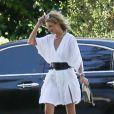 Rosie Huntington-Whiteley à Beverly Hills, porte une jolie robe blanche, une ceinture en cuir Isabel Marant, un sac Givenchy (modèle Shark Tooth) et des sandales Chloé (collection printemps-été 2015). Le 24 mai 2015.