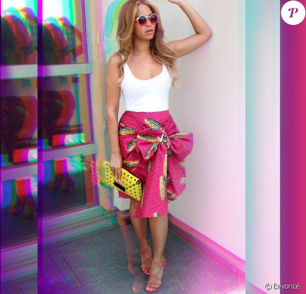 Beyoncé porte des lunettes de soleil Quay, un débardeur blanc, une jupe Stella Jean (modèle Dugongo, collection printemps-été 2015), un sac Milli Millu et des sandales Alaïa. Mai 2015.