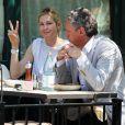 """Exclusif - Kelly Rutherford fait un signe """"peace"""" aux photographes alors qu'elle déjeune en terrasse du restaurant Sant Ambroeus avec un ami à New York, le 5 mai 2015."""