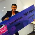 Christophe Beaugrand pose avec le chèque de 100 000 euros destiné à Emilie, grande gagnante de Secret Story 9. Le 19 novembre 2015.