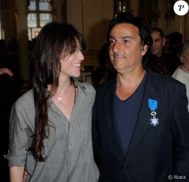 Yvan Attal pose avec Charlotte Gainsbourg, après avoir reçu les insignes de chevalier de l'Ordre National du mérite au ministère de la Culture à Paris le 19 juin 2013