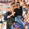Les soeurs Kardashian retombent en enfance ! Kourtney et Khloé font un tour de carrousel à Encino. Le 23 août 2016.