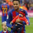 Le footballeur du FC Barcelone Neymar pose avec son fils Davi Lucca ( blond) et un bébé à Barcelone le 4 février 2017