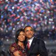 Michelle Obama, dans les bras de son cher et tendre, lors de son discours à la convention nationale démocratique en août 2008, porte une robe rouge et noire réhaussée d'une petite broche.