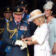 Le prince Charles se fait aider par son épouse Camilla Parker Bowles avec ses gants à l'abbaye de Westminster, le 10 juillet 2018 à Londres, lors du service marquant le centenaire de la Royal Air Force (RAF).
