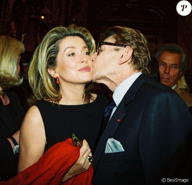 """Catherine Deneuve, Yves Saint Laurent lors du défilé """"Yves Saint Laurent"""" collection Haute Couture Automne-Hiver 1999/2000 à Paris, le 21 juillet 1999."""
