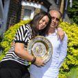 Marion Bartoli (avec son trophée de Wimbledon) et son père Walter à Londres, le 8 juillet 2013