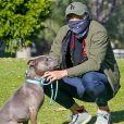 Exclusif - Henry Golding, équipé d'un foulard en guise de masque, promène son pitbull Stella dans un parc, en marge du confinement à Santa Monica, le 23 avril 2020.