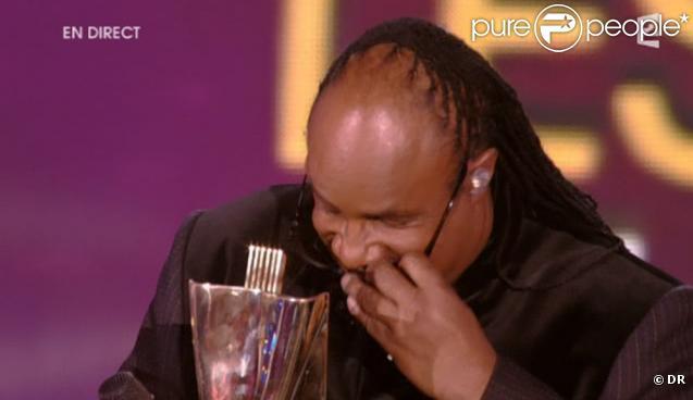Stevie Wonder enlève ses lunettes un court instant, le temps de regarder sa jolie récompense.