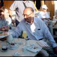 Jacques Chirac se détend sur le port de Saint-Tropez avec un bon verre et une foule de badauds qui viennent le saluer le 5 août 2010