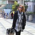 Jessica Alba dans un look chilly pour voyager, avec sa valise Rimowa. Aéroport de Los Angeles.